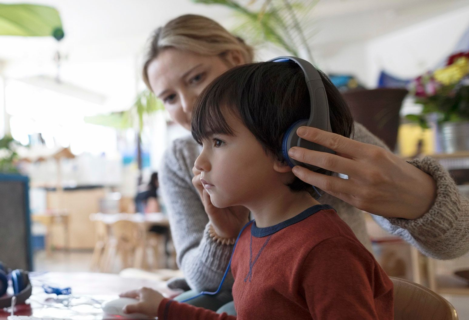 A woman holds headphones over a young boy's ears. He listens to the hearing test.