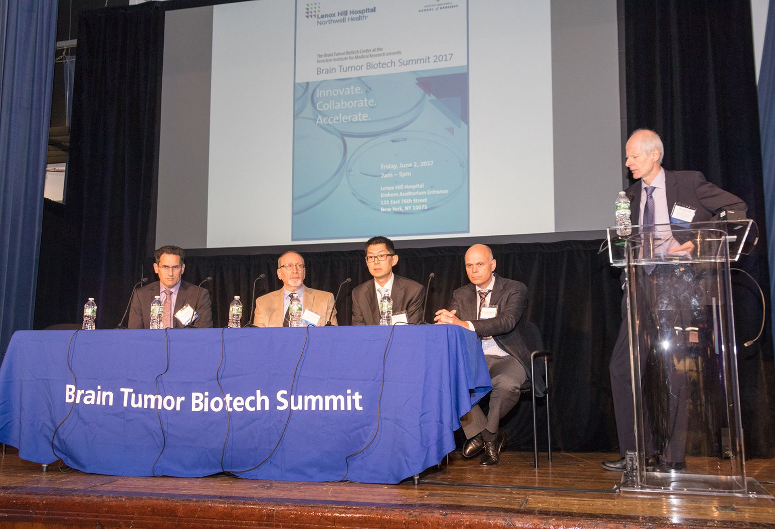 Panel of 5 professional men on stage at a conference