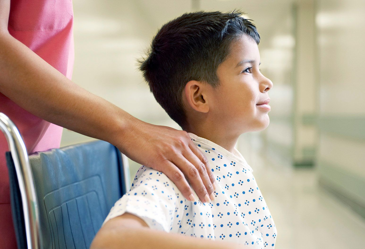 A boy around 10 years old sits in a wheel chair in the hospital, looks up and smiles. A woman has her hand on his shoulder.