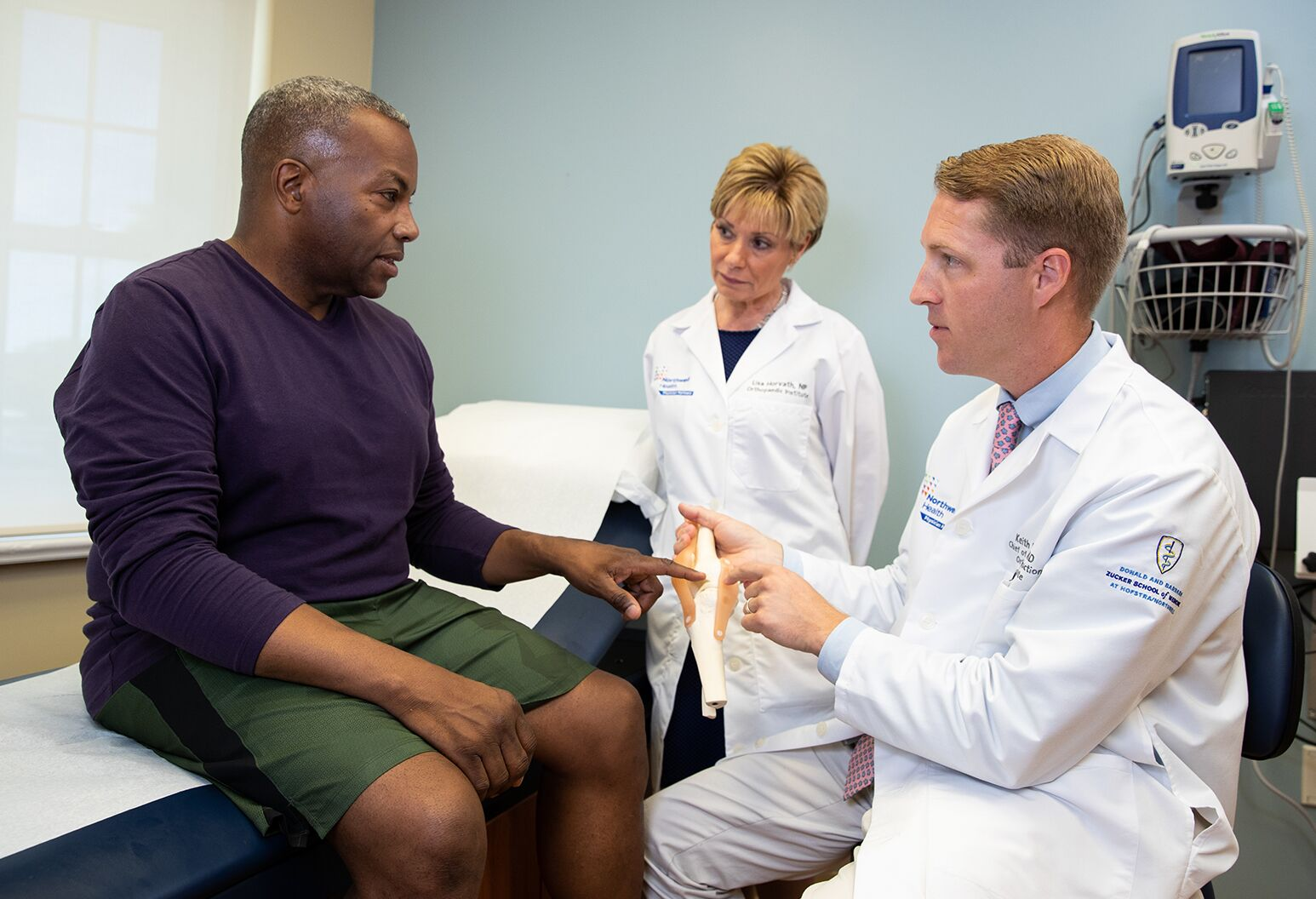 Doctor is showing a model of a knee to a middle aged male patient