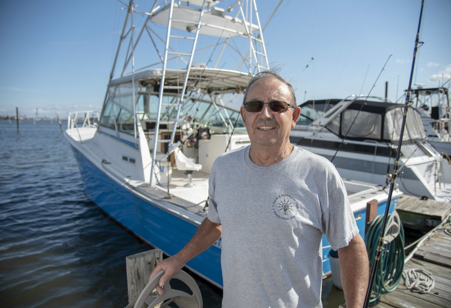Jose Freire stands on a wooden dock in front of his boat, the Estrella del Mar. His LINQ cardiac recorder has allowed him to receive treatment for his heart arrhythmia and return to his beloved hobby of fishing.