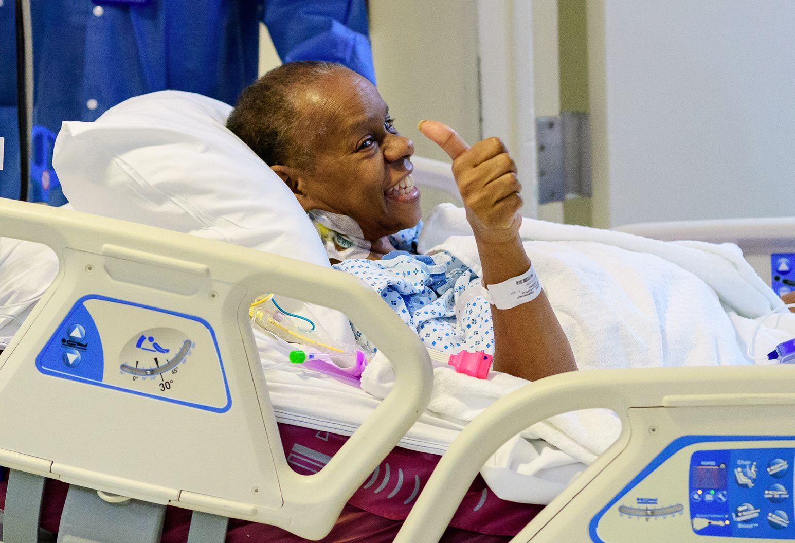 A smiling elderly woman in a hospital bed gives a thumbs up.