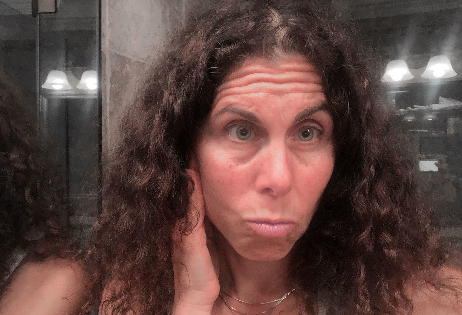 A woman with long dark and curly hair stands in front of a bathroom mirror and looks at her reflection. Her hand is on the side of her face along her jawline.