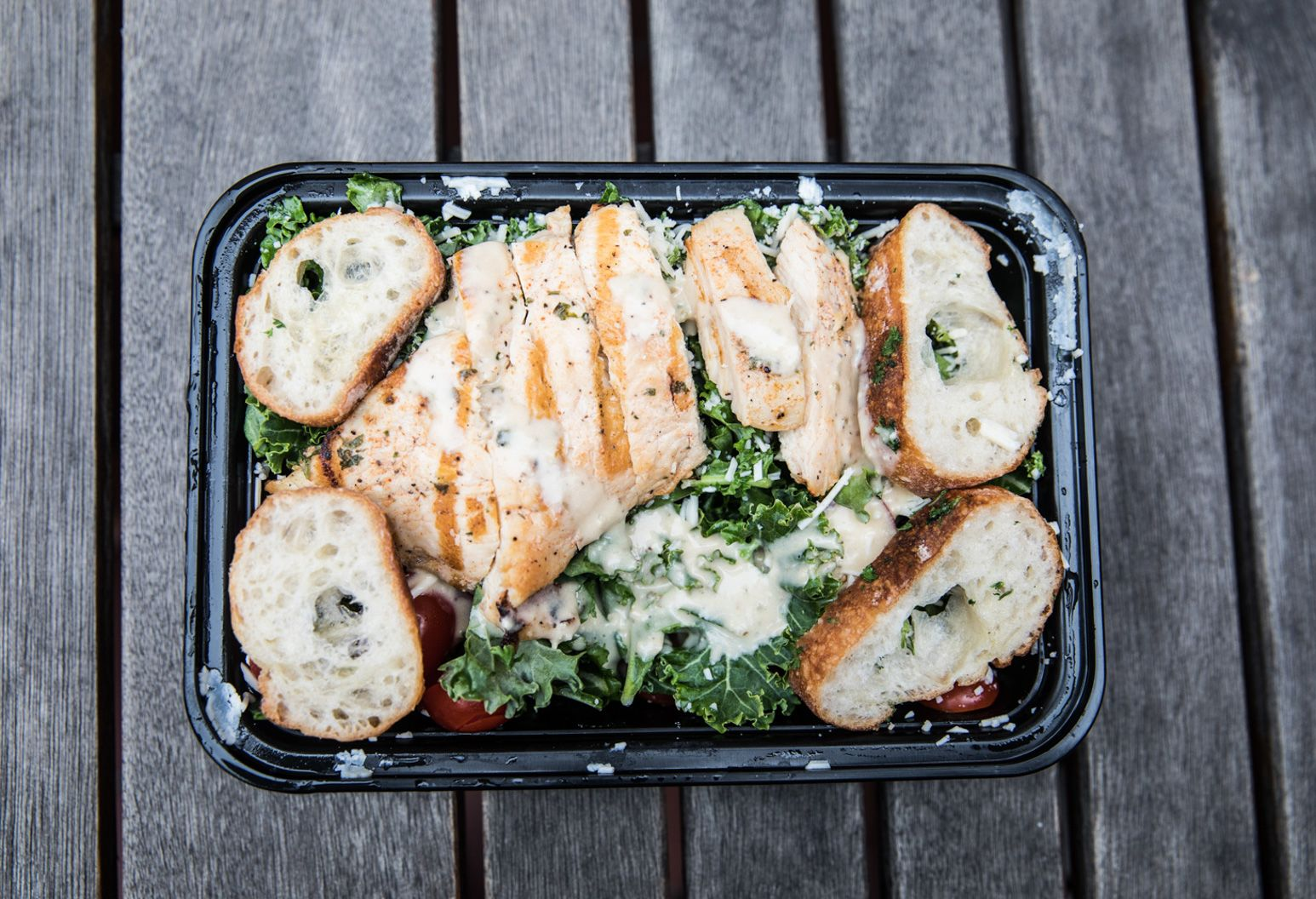 A black plastic container contains sliced grilled chicken pieces sitting next to small slices of bread over a kale salad with a small amount of white dressing over the top of the dish.