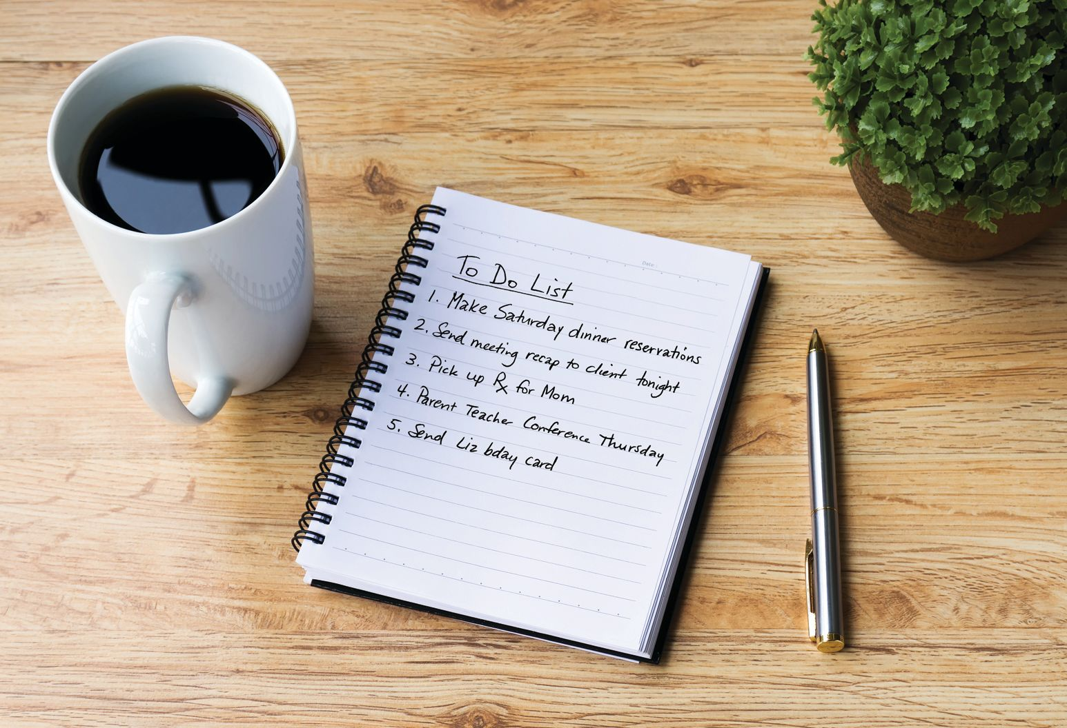 "White mug is filled with coffee on a wooden table next to a small notebook that says ""To Do list"" followed by a list of 5 items that starts with ""Make Saturday dinner reservations"""