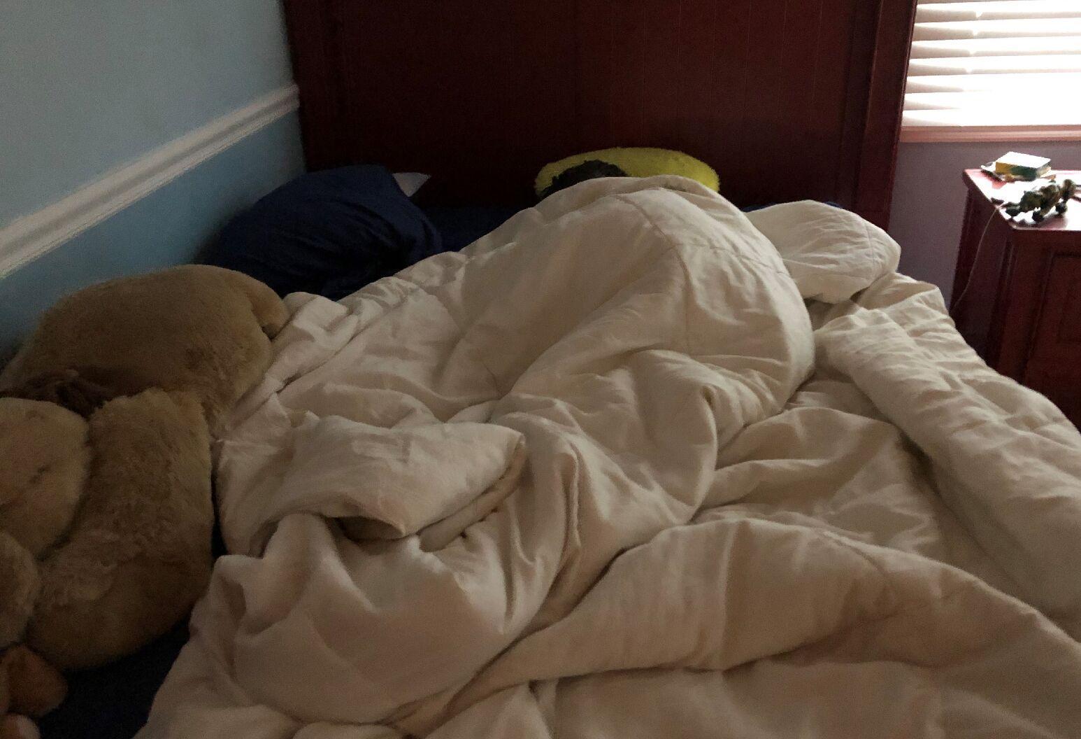 A boy sleeping in bed underneath a blanket