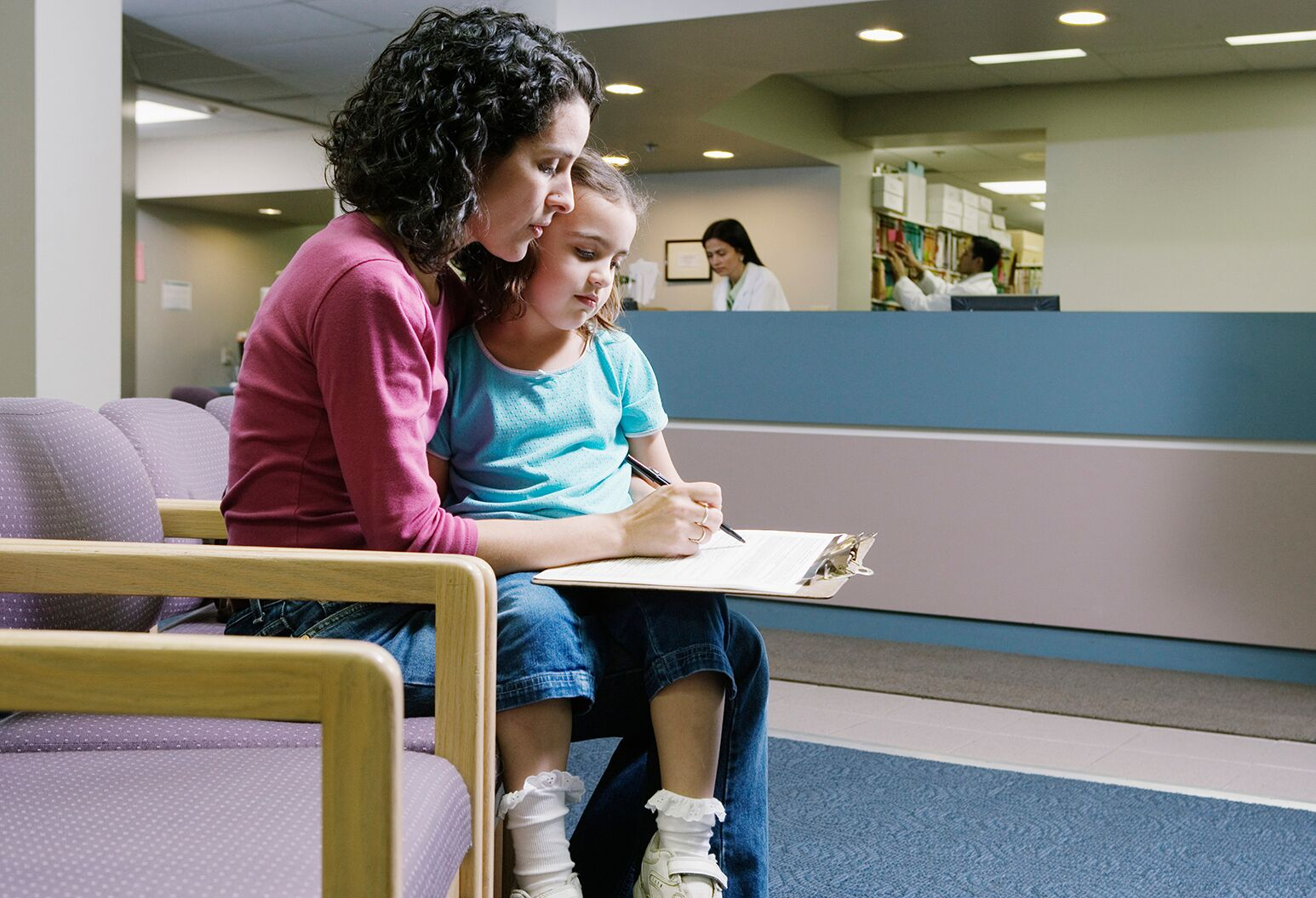 A woman holds a young girl on her lap while filling out forms.