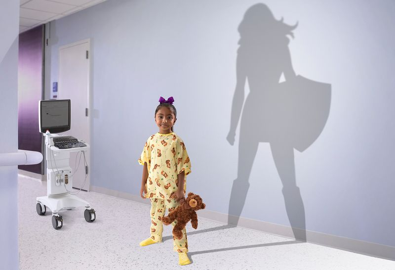 In a hospital room, a five year old girl stands tall wearing yellow pajamas and holding a stuffed bear. Her shadow is cast on the wall behind her, and the shadow resembles a larger-than-life female super hero carrying a shield.