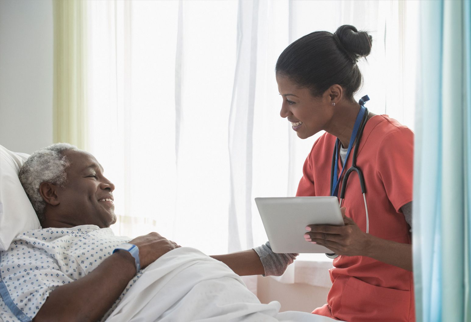 An elderly man laying in bed is being looked after by a care professional wearing a stethoscope and holding a tablet.