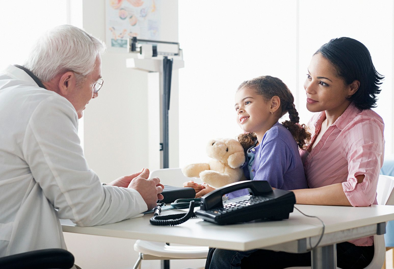An elderly male doctor sits in a doctors office across the table from a little girl and her mom. The little girl has her hair in pigtails and is holding a teddy bear and looking at the doctor.