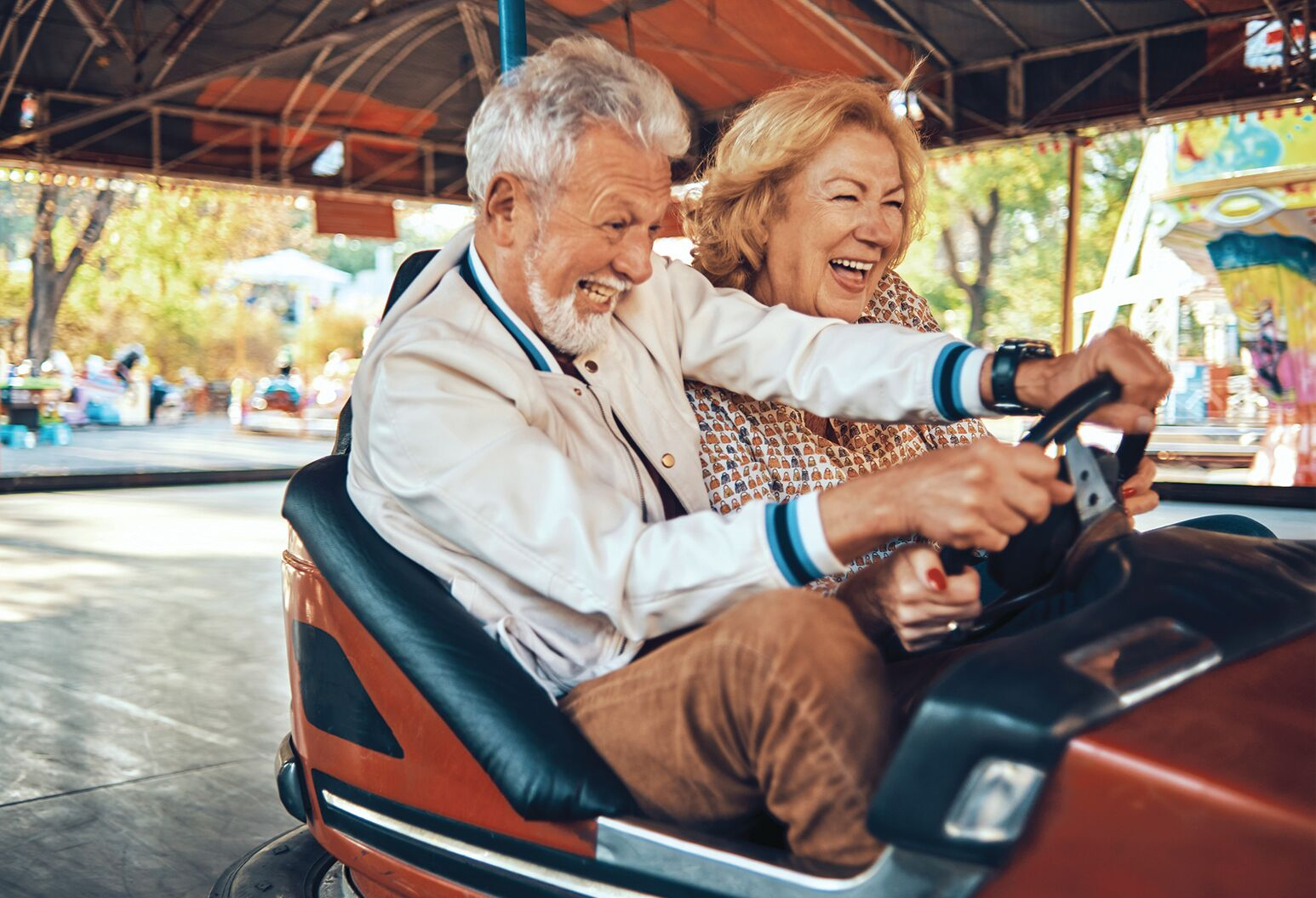 An elderly man and woman smiling in a bumper car