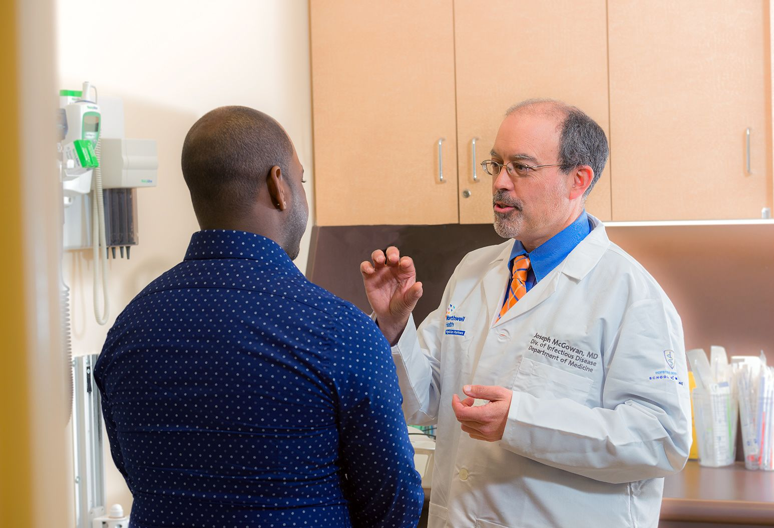 A male doctor in a white lab coat and glasses spends one-on-one time with a male patient, explaining something to him using hand gestures.