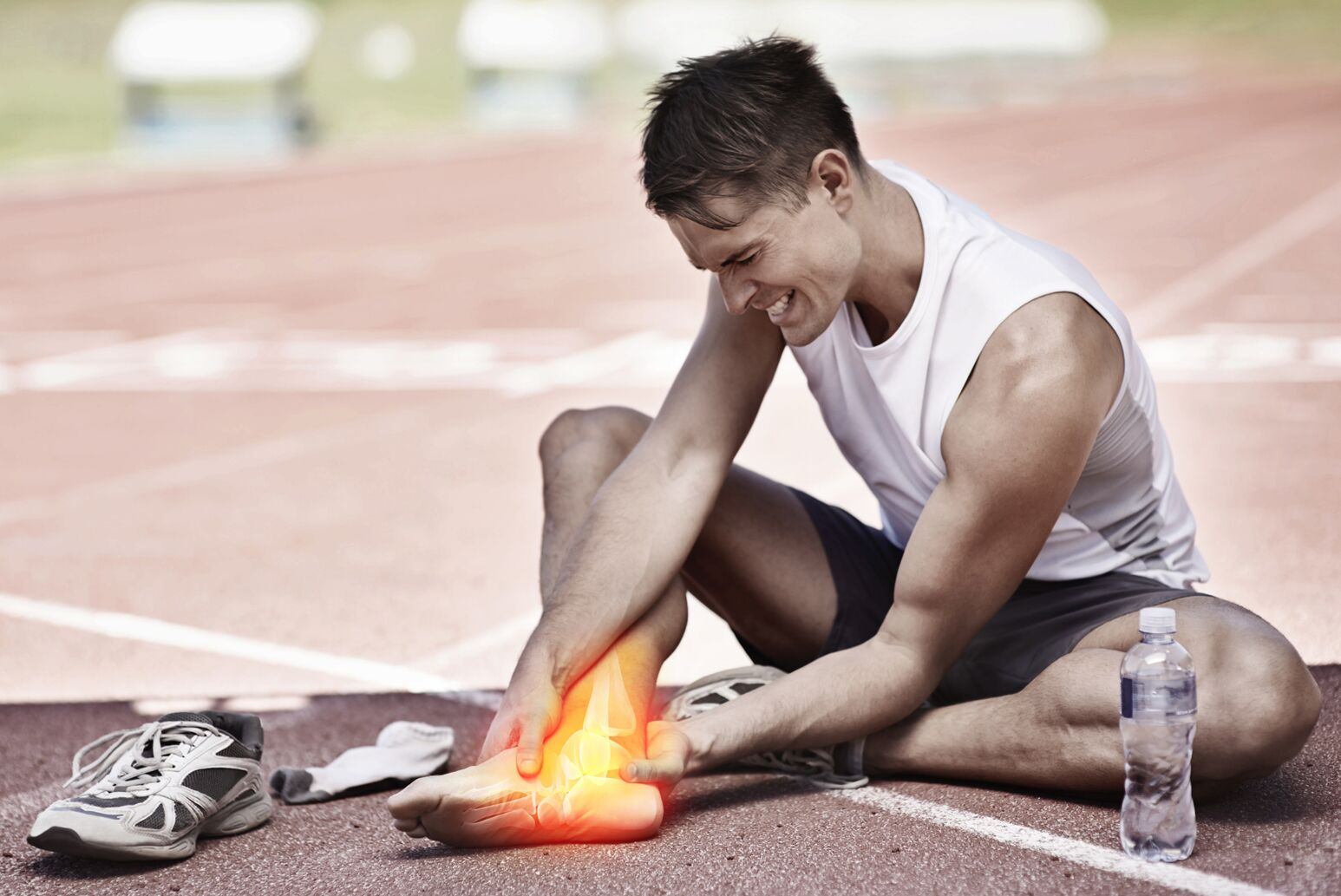 A runner holds his ankle after an injury.