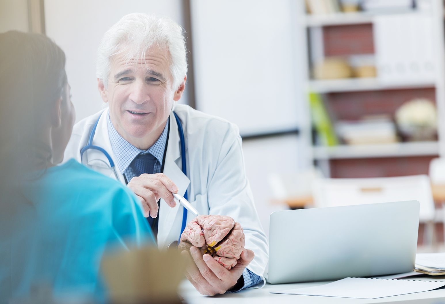 Confident Caucasian senior male neurosurgeon consults with a colleague about a patient's diagnosis. The male doctor is holding a human brain model.