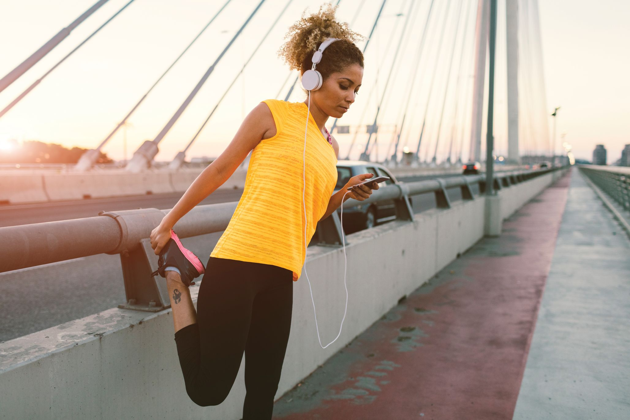 A 20 year old woman with curly hair is wearing a yellow tank top, black leggings and sneakers. She has a music device in her hand with earbuds connected to it and in her ears. She is stretching her quads in the running lane of a bridge.