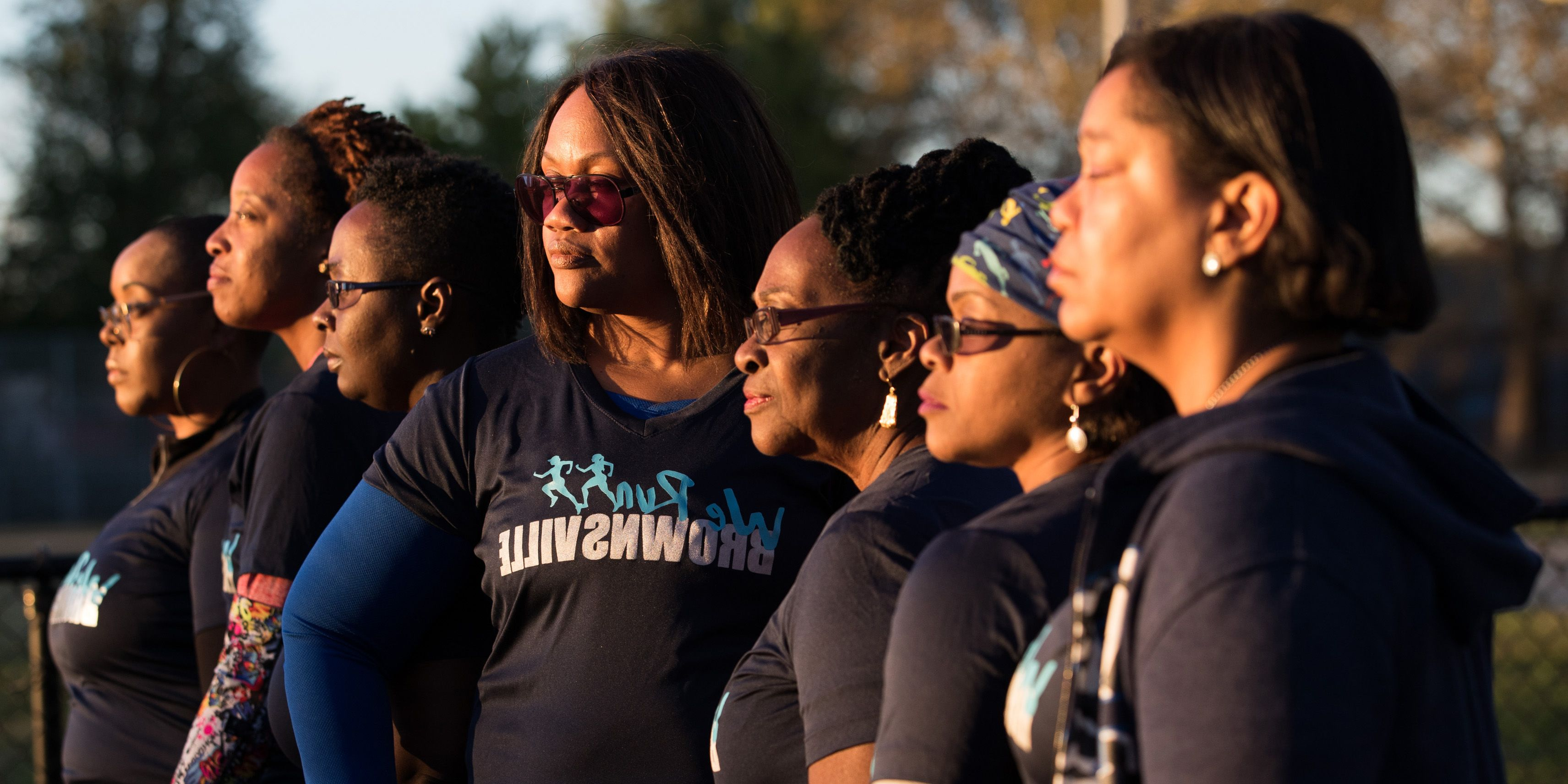"Seven women stand in a line looking off to the left. They wear matching blue t-shirts that say ""We Run Brownsville."""