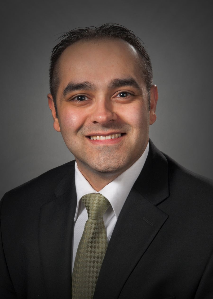 Sandeep Kapoor, MD, wearing a dark suite and green tie