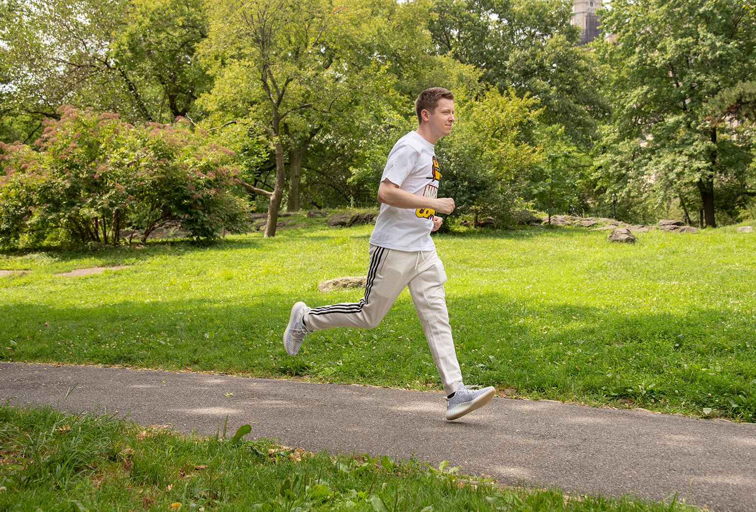 Young man who suffered a stroke at age 21 in white sweatpants and shirt running in Central Park