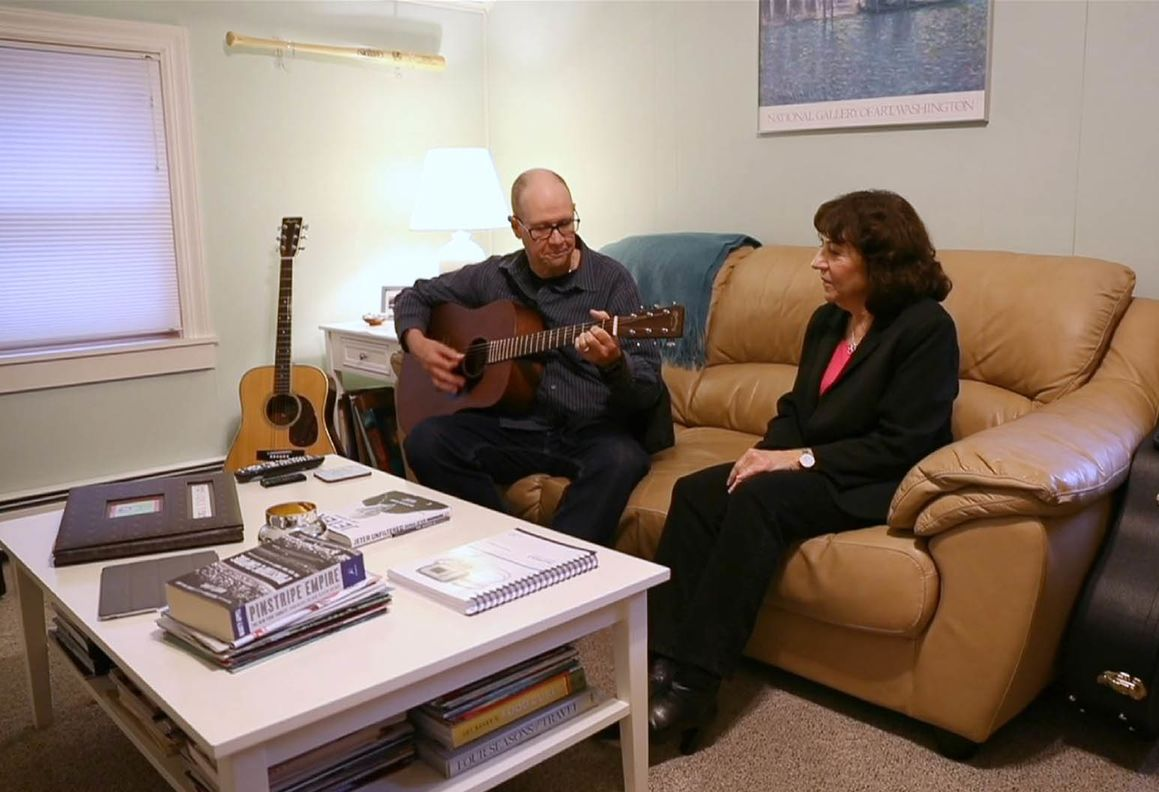 A man sits on a couch playing a guitar. A woman sits next to him and watches on.