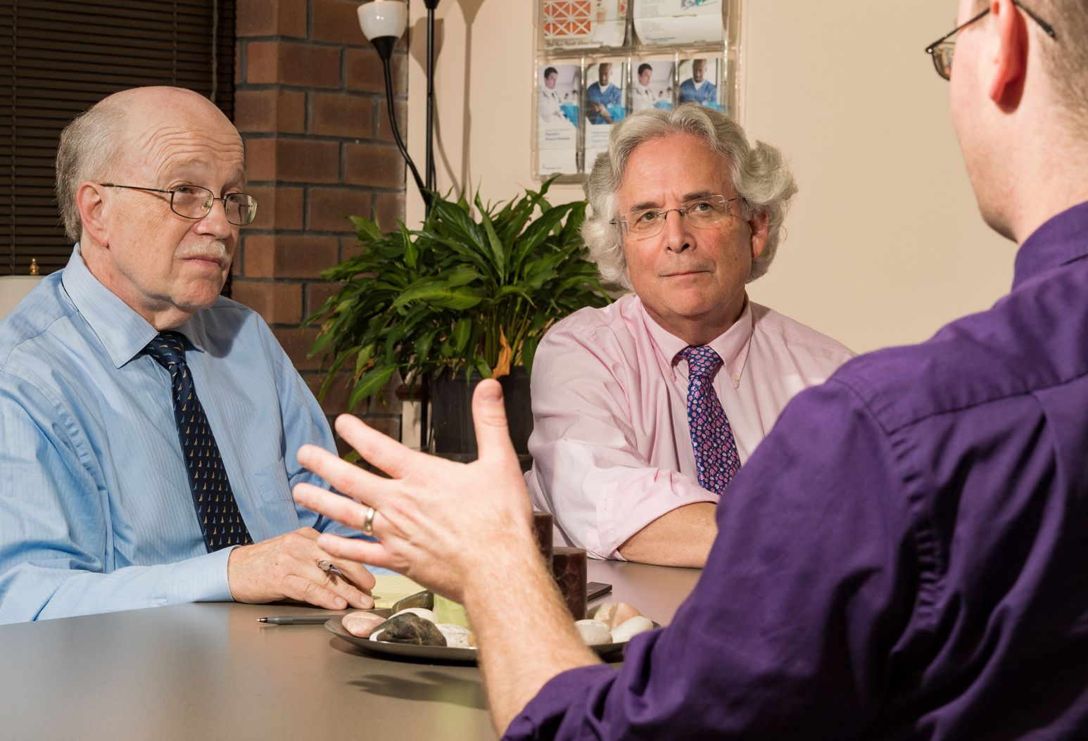 Curtis Reisinger, PhD, and Jeffrey Selzer, MD, consult a patient