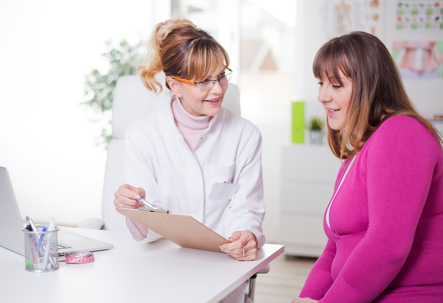 Female doctor wearing white lab coat is sitting at a desk showing a medical chart to a female patient wearing a pink sweater