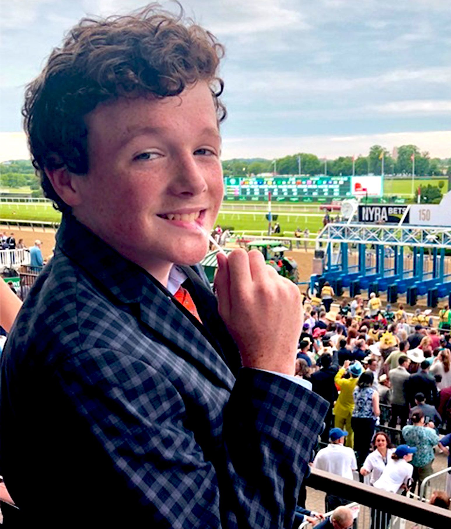 Young teenage boy with curly hair sits in the stands of a horse race track. He smiles for the camera while holding a lollipop in his mouth.