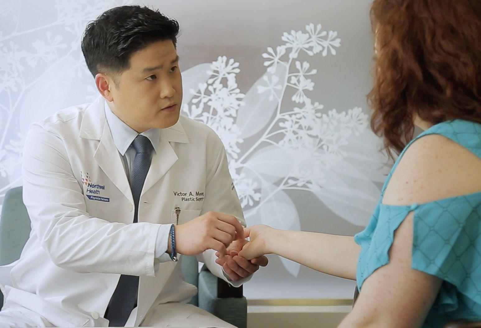 Plastic surgeon examining patients hand