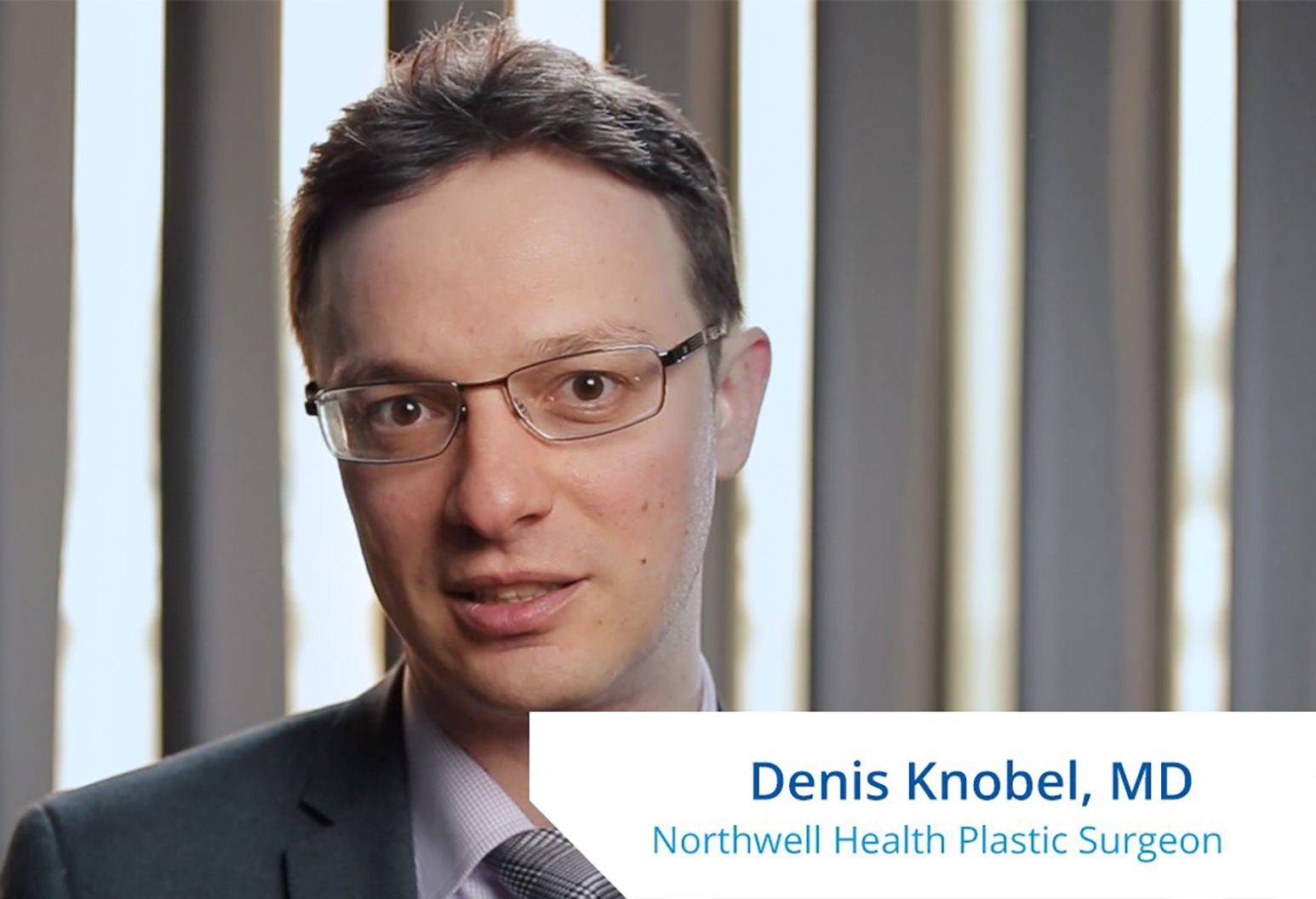 """A man with short brown hair and wearing glasses speaks to the camera. On the lower right corner of the photo it reads, """"Denis Knobel, MD. Northwell Health Plastic Surgeon."""""""