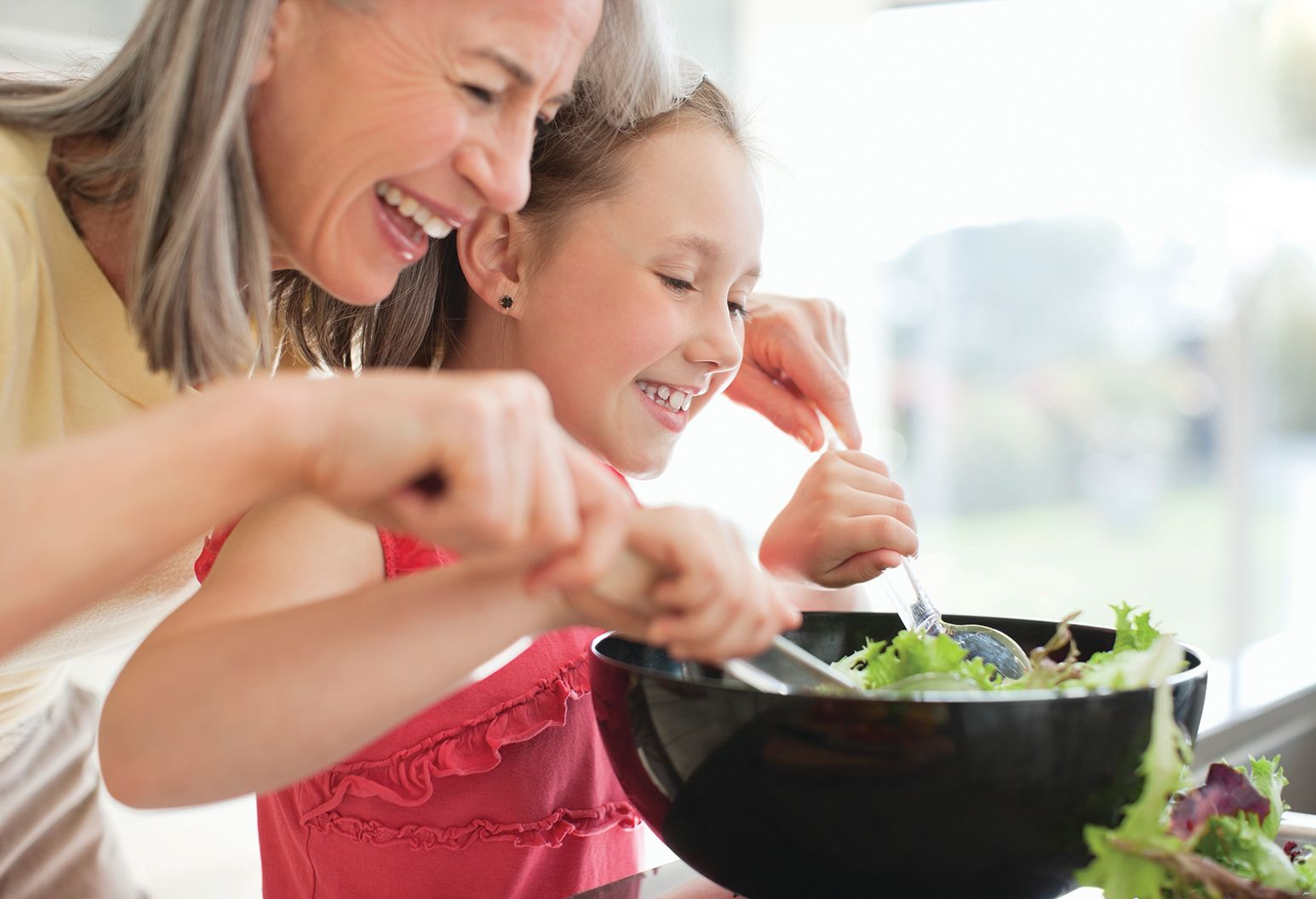 Grandmother and granddaughter preparing salad