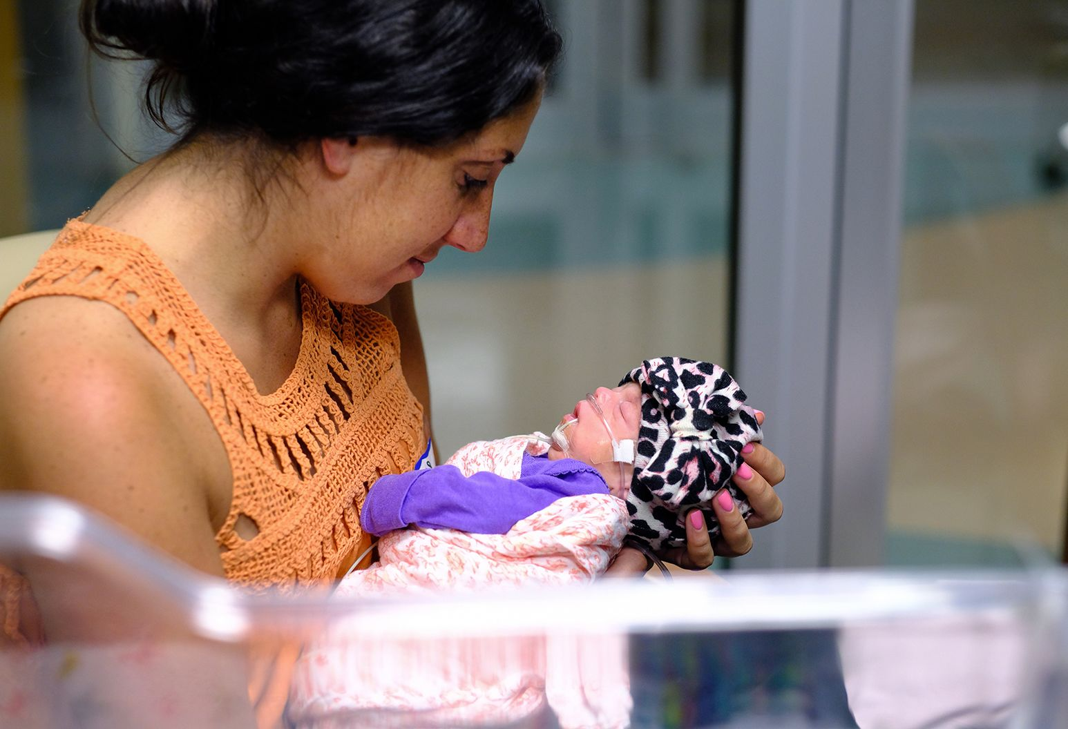 Woman in orange shirt holding infant baby in the hospital.