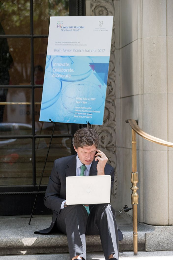 Middle aged man wearing a suit is sitting on the steps outside a building talking on the phone and looking at his computer