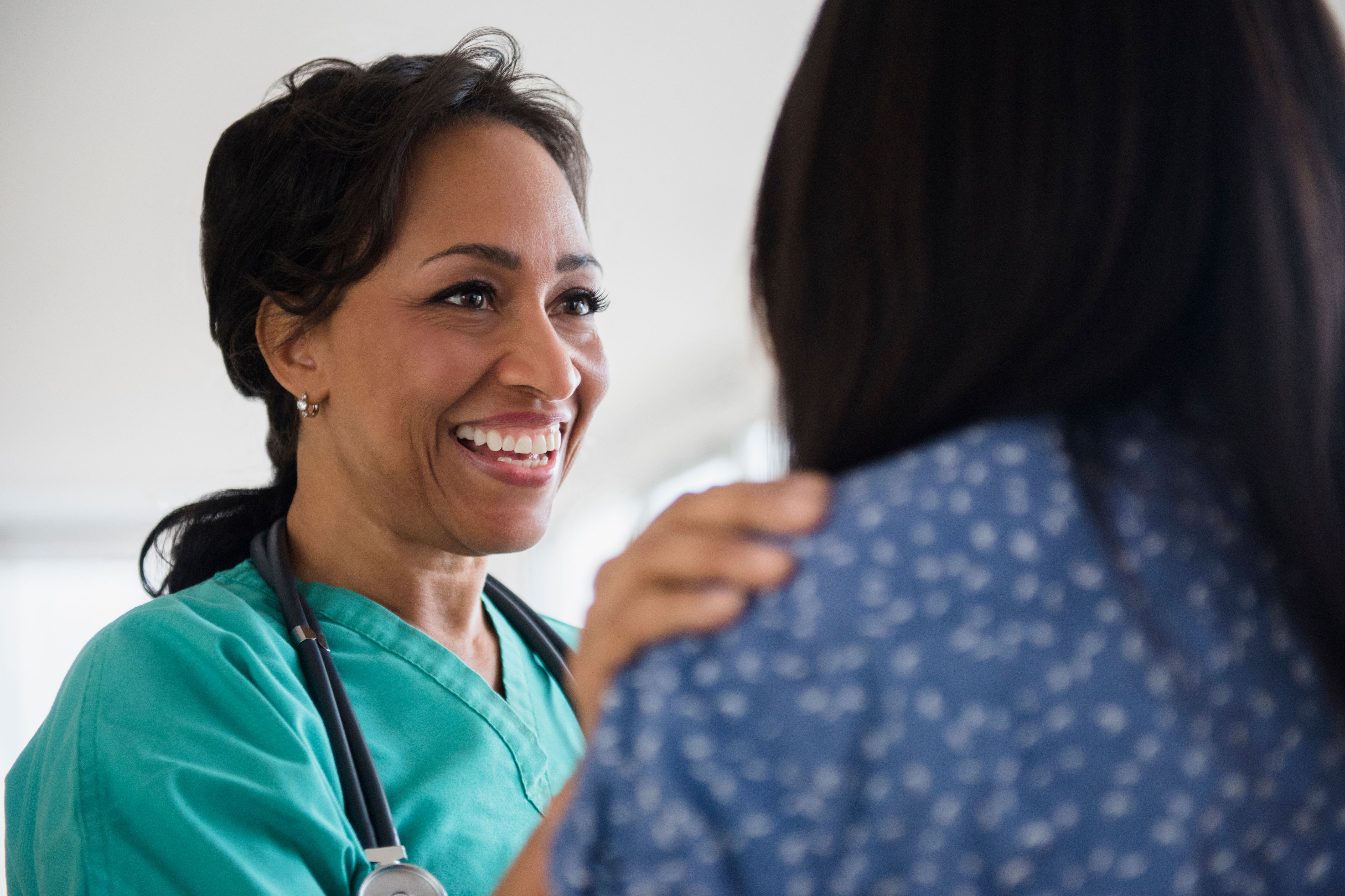 Smiling nurse wearing scrubs comforting a patient.