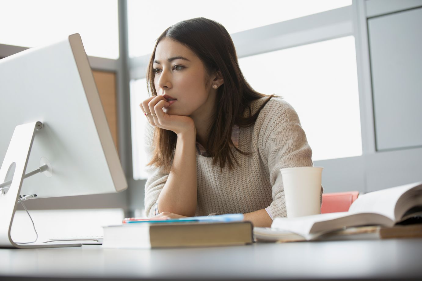 woman sitting at desk, resting her face on her hand, looking at computer