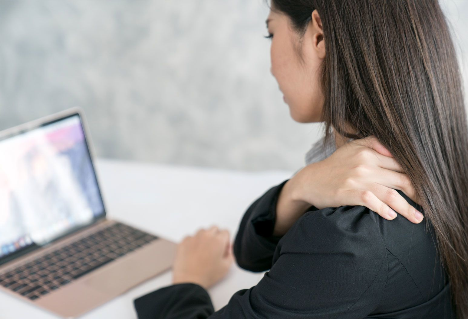 A young woman sits at a laptop and is holding her shoulder as if she is in pain. She's wearing a black shirt and has long brown hair.