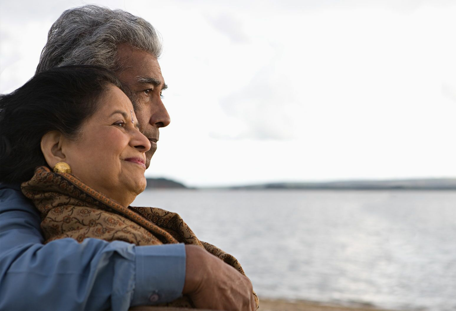 An elderly man and woman embrace with the sea in the background of the shot.