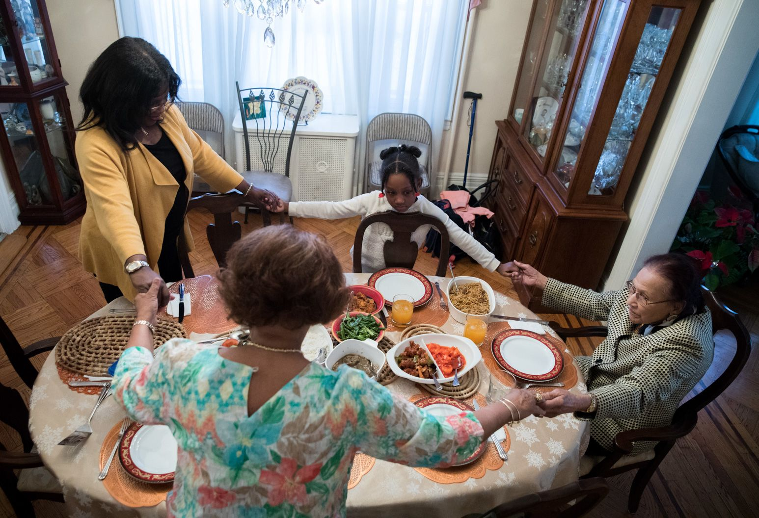 Two woman, a young child, and an older woman are praying while holding hands around a dining table.
