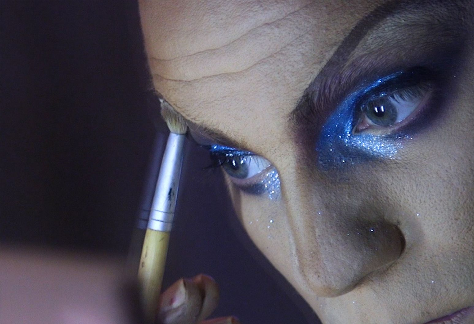 Close up of a man's face putting on make up. His eyes have blue and silver glitter around it and his face is powdered white.