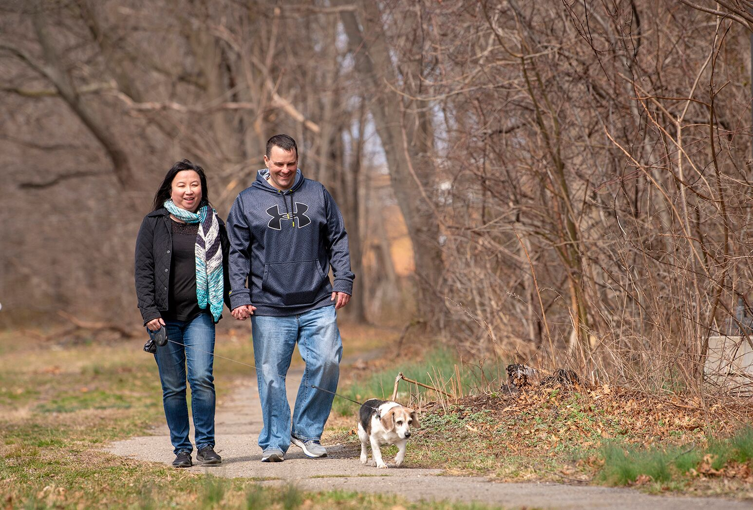 Couple walking their beagle on a winter day.