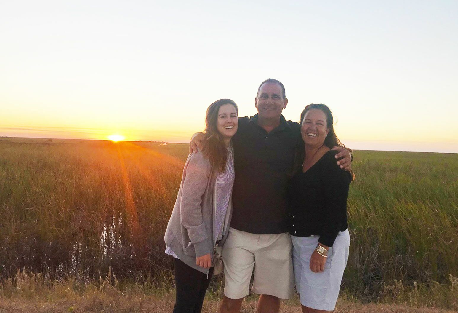A man smiles with his arms around two women next to him as they stand against the sunset.