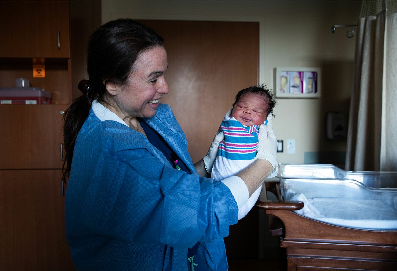 A woman with dark hair tied up in blue scrubs holds a newborn baby toward the camera swaddled in a hospital wrap. The baby is letting out a faint smile.