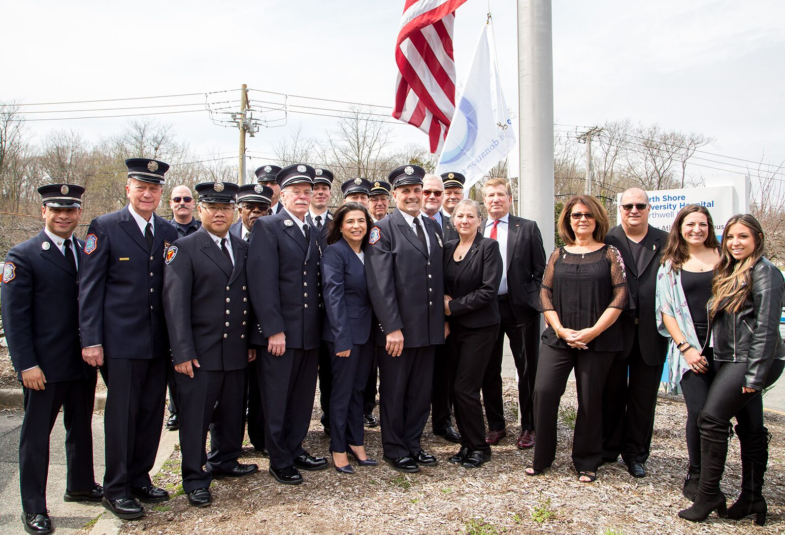 Northwell Health leadership, joined by State Senator Anna Kaplan (center) , donor families and volunteer firefighters gather for a flag-raising event at North Shore University Hospital to honor organ and tissue donors and their loved ones.