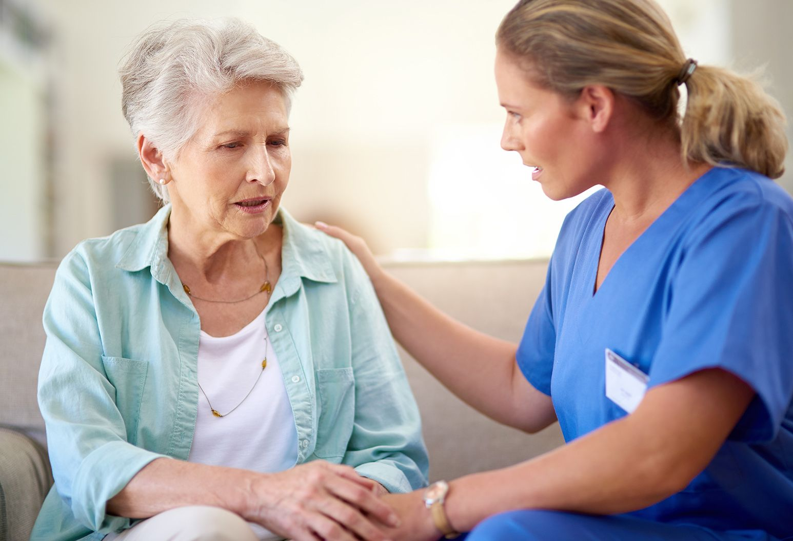 Shot of a caregiver consoling a senior patient in a nursing home