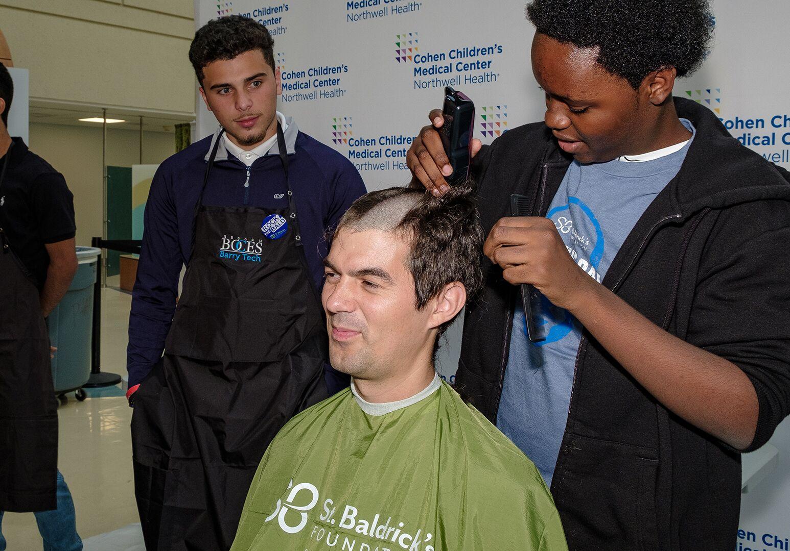 "Cohen Children's chaplain Adrian Mazur ""rocks the bald"" with the assistance of patient Nicholas Williams, of Jamaica, Queens."