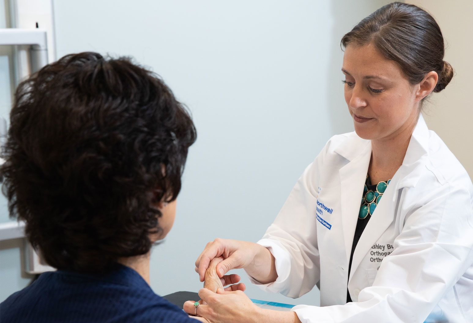 A female doctor examines a female patient's hand. The doctor has brown hair pulled back in a bun and wears a Northwell branded white coat.