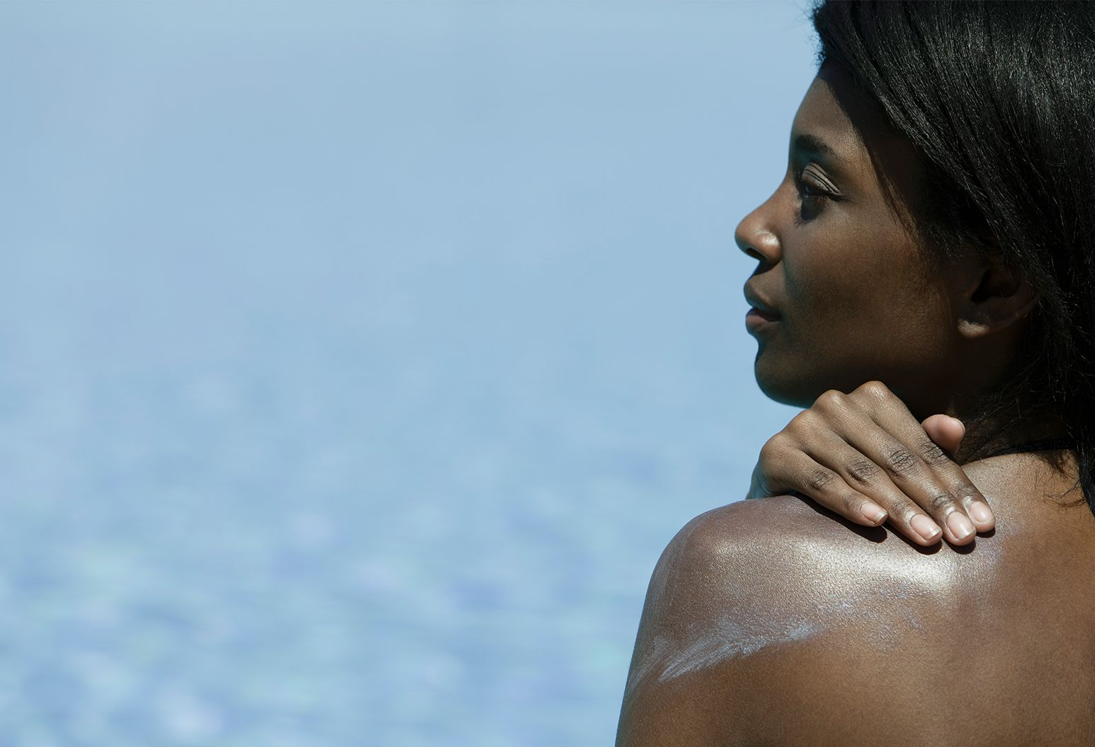 Woman sitting on beach with sunblock on her back. For Dear Doctor article on The Well.