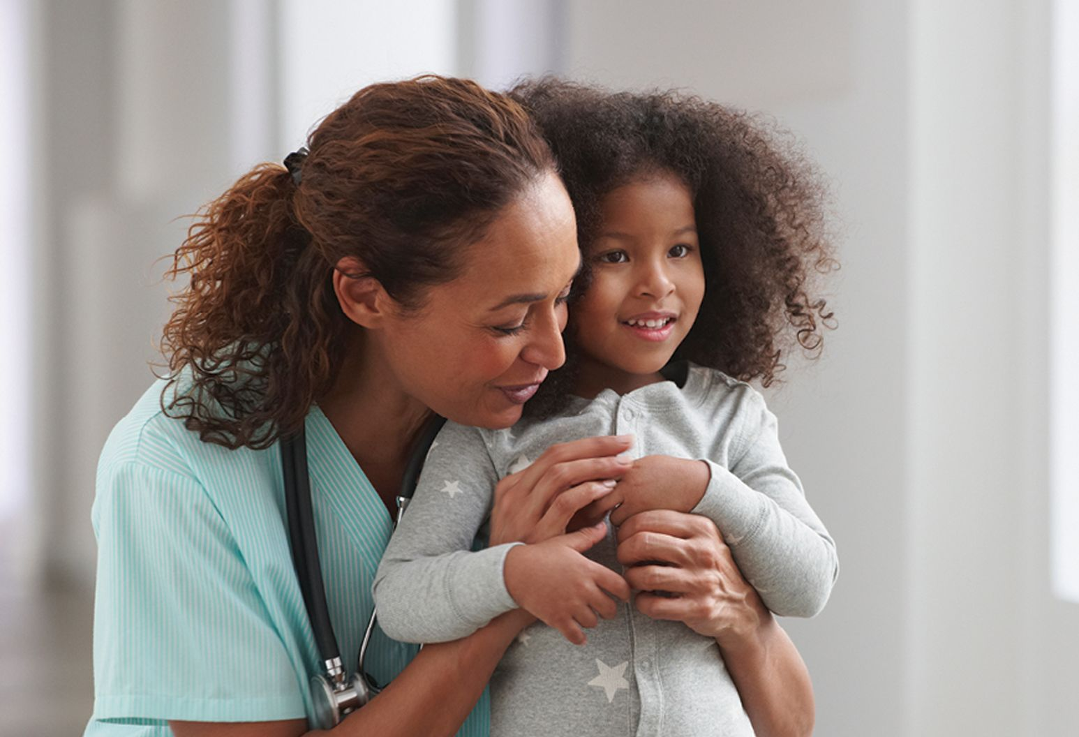 nurse hugging a small child from behind