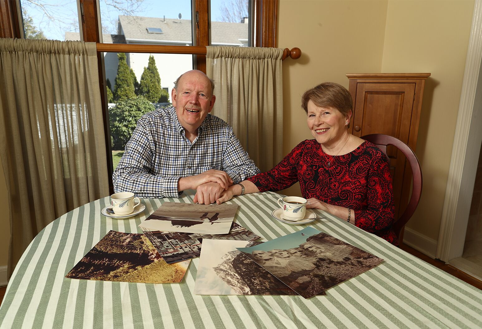 Older couple sits in their dining room holding hands with a display of photographs on the table.