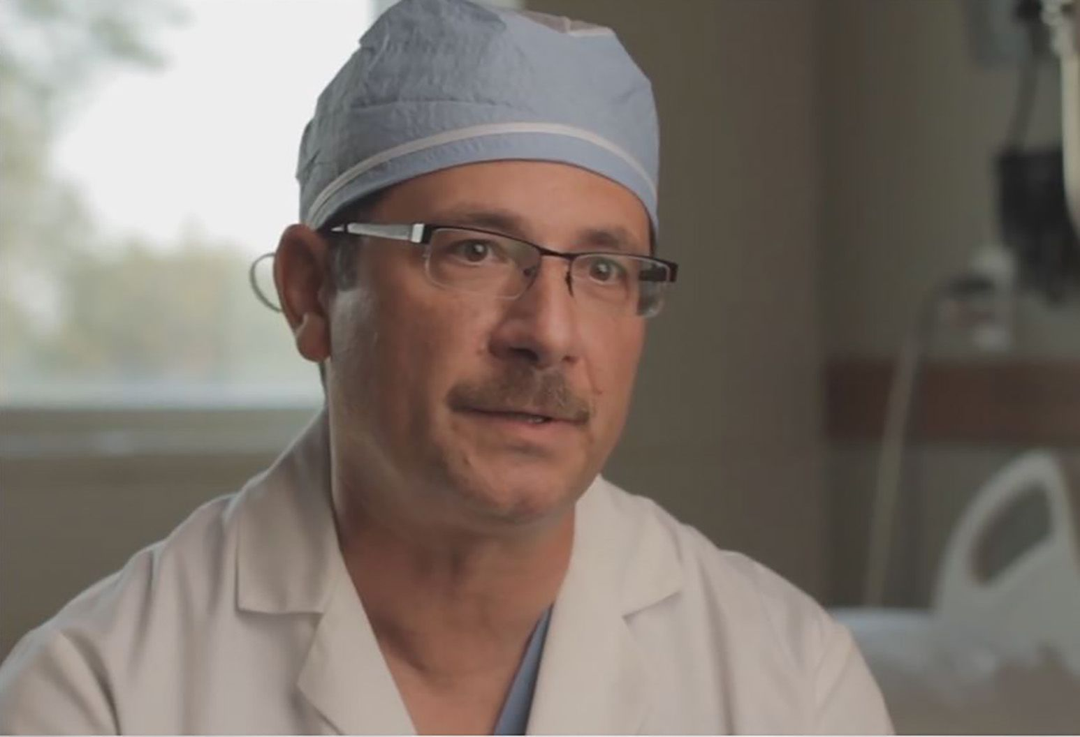Dr. Vincent Leone wears a white lab coat, blue surgical hat and glasses and looks at the camera, about to speak.