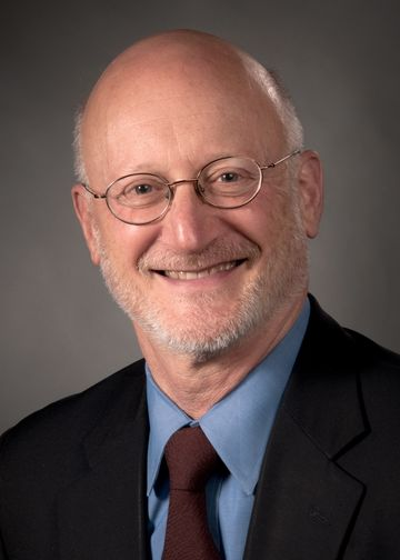 John Kane, MD, wearing a blue shirt and maroon tie