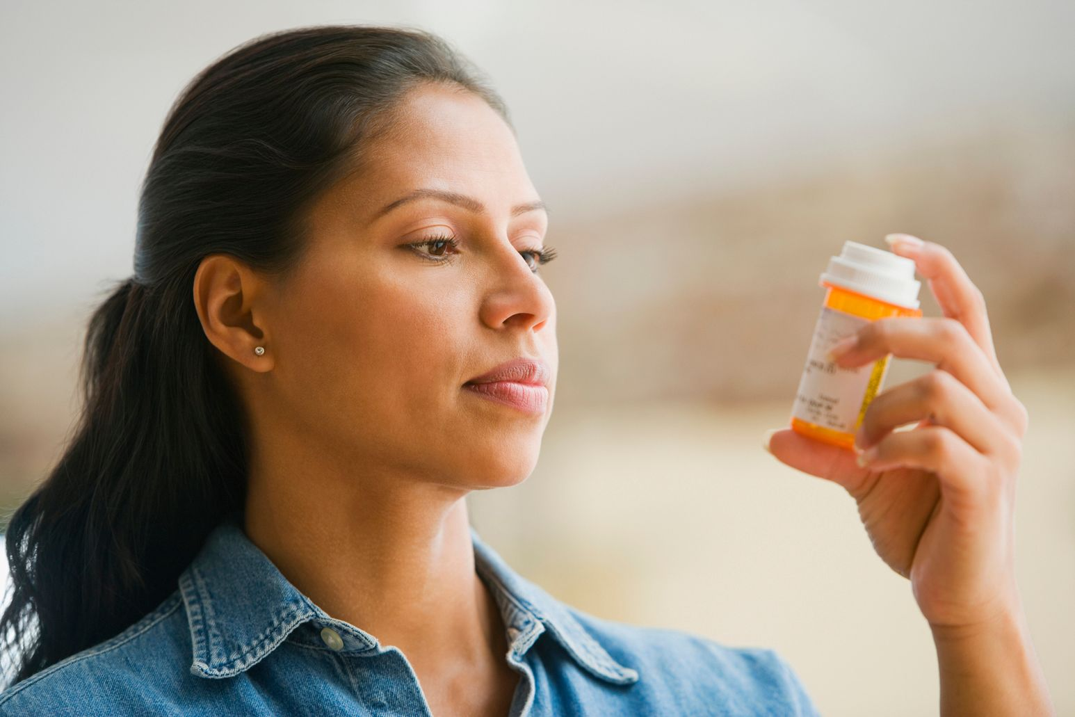 A woman looks at a pill bottle